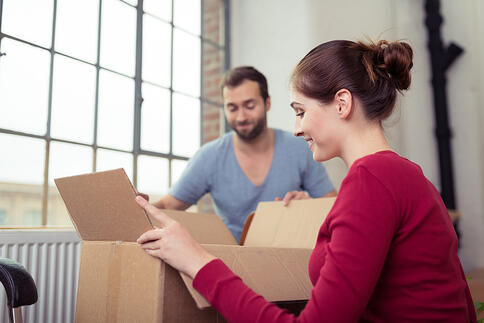 Attractive young couple moving house getting ready to unpack a cardboard carton of personal possessions below a big window