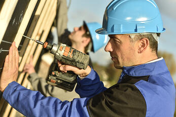 Construction worker using electric drill on building site-1