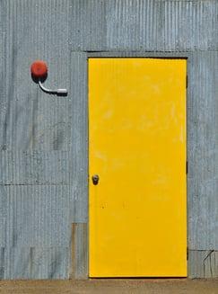 Industrial exterior yellow door with alarm bell