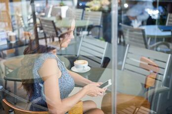 Pretty woman using her phone having a coffee in a coffee shop