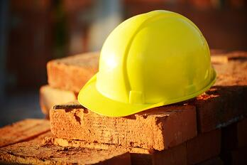 Hard hat on a brick wall.