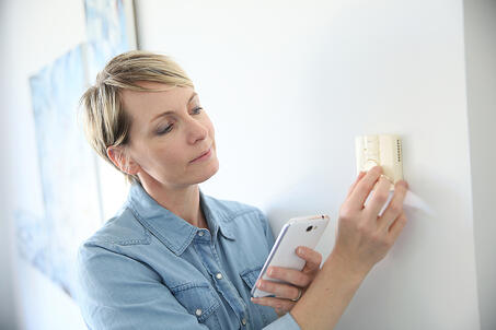 Woman porgramming indoor temperature with smartphone application-2