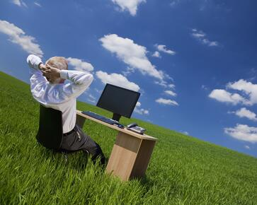 Man sitting at his desk in a field admiring a blue sky
