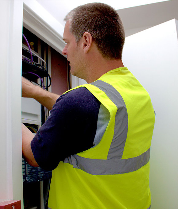 Electrician in high viz jacket working on an electrical installation