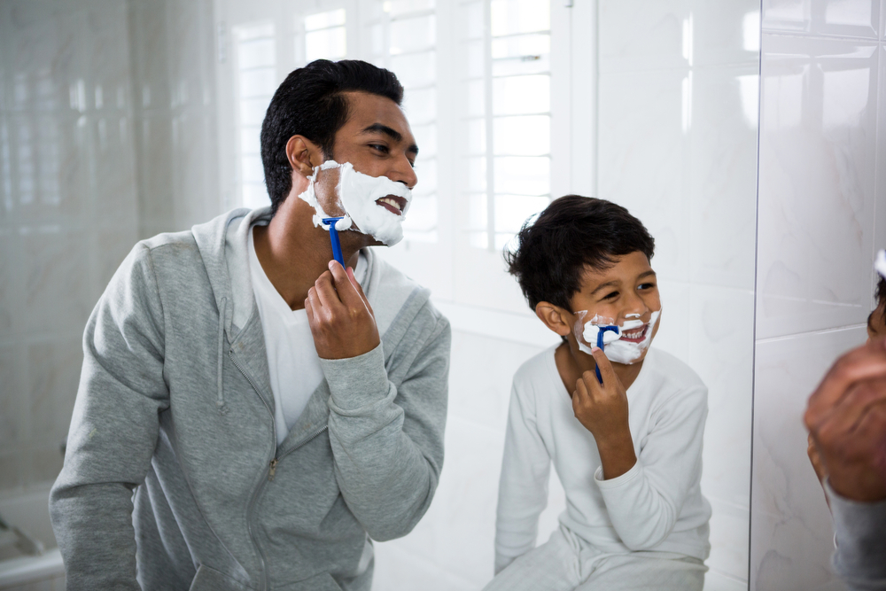 Father and son shaving together in the bathroom at home
