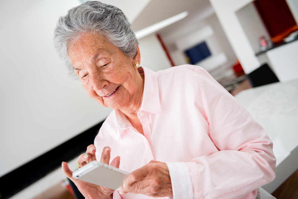 Happy senior woman using app on a cell phone-1