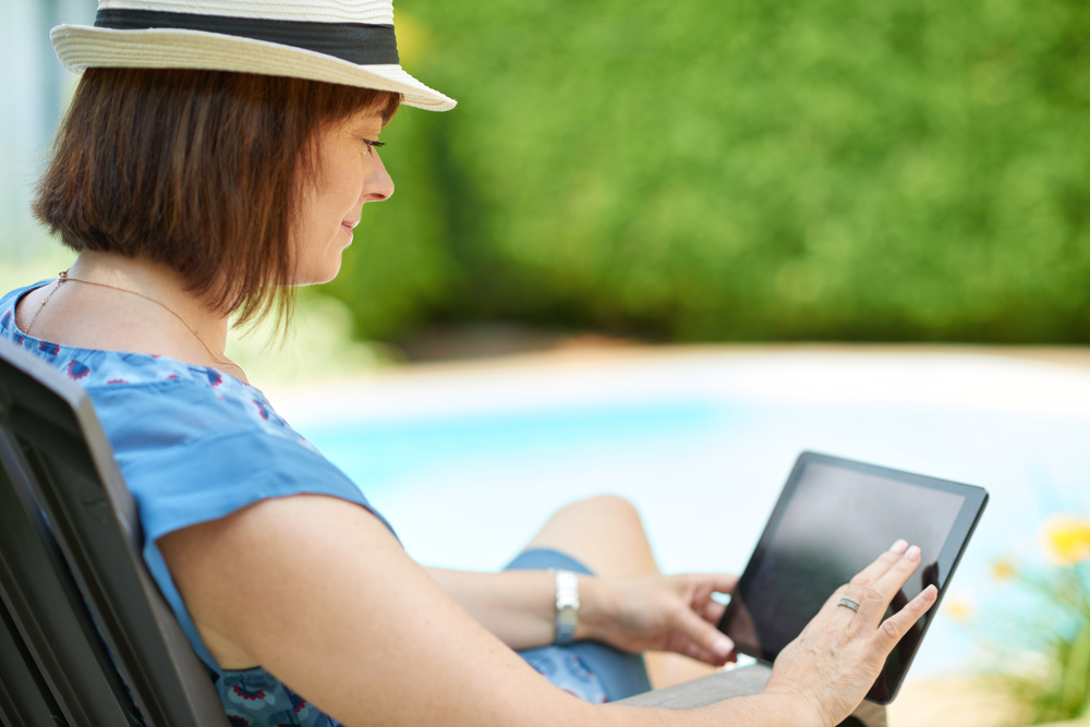 Mature woman using digital tablet wearing a fedora hat