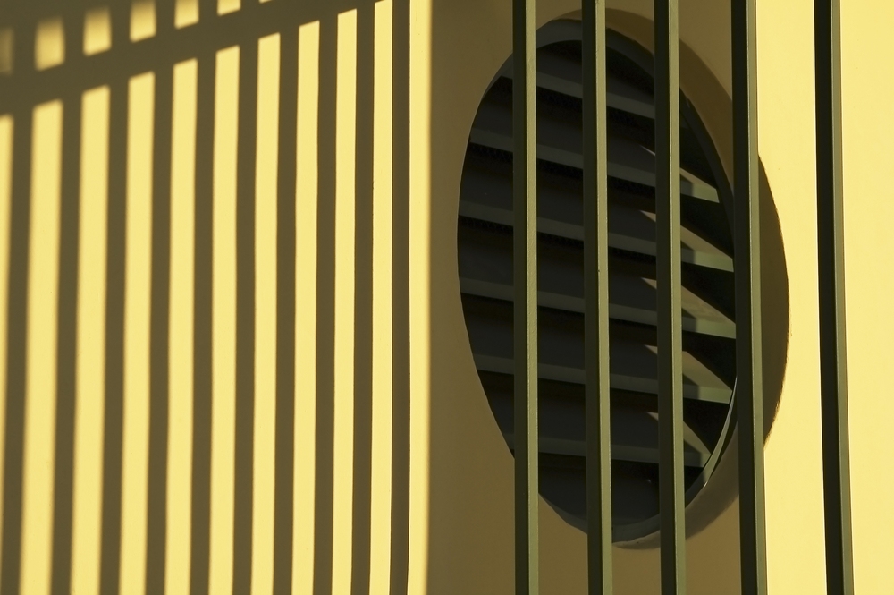 Ventilator and shadows of iron fence on exterior wall